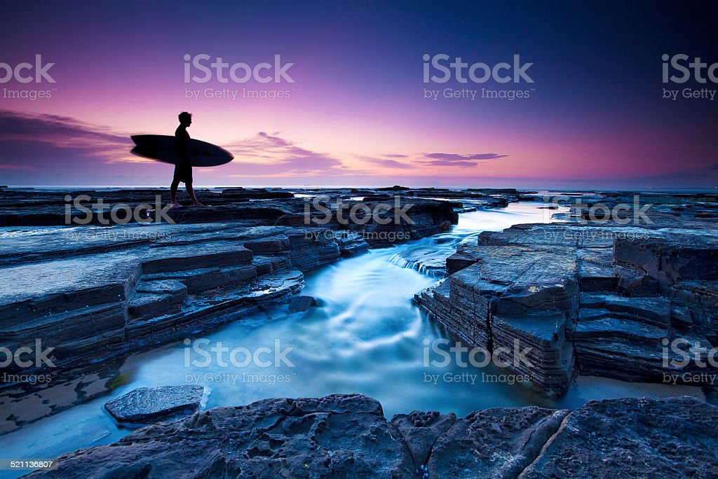 Surfer before dawn stock photo