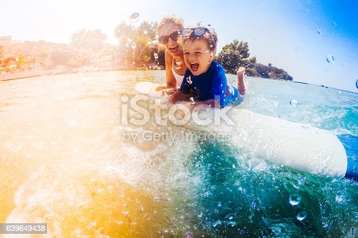istock Surfer boy and his mom having fun in the sea 639649438