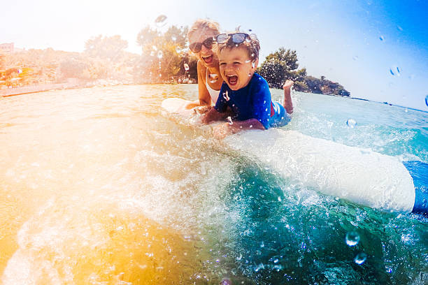 Surfer boy and his mom having fun in the sea stock photo