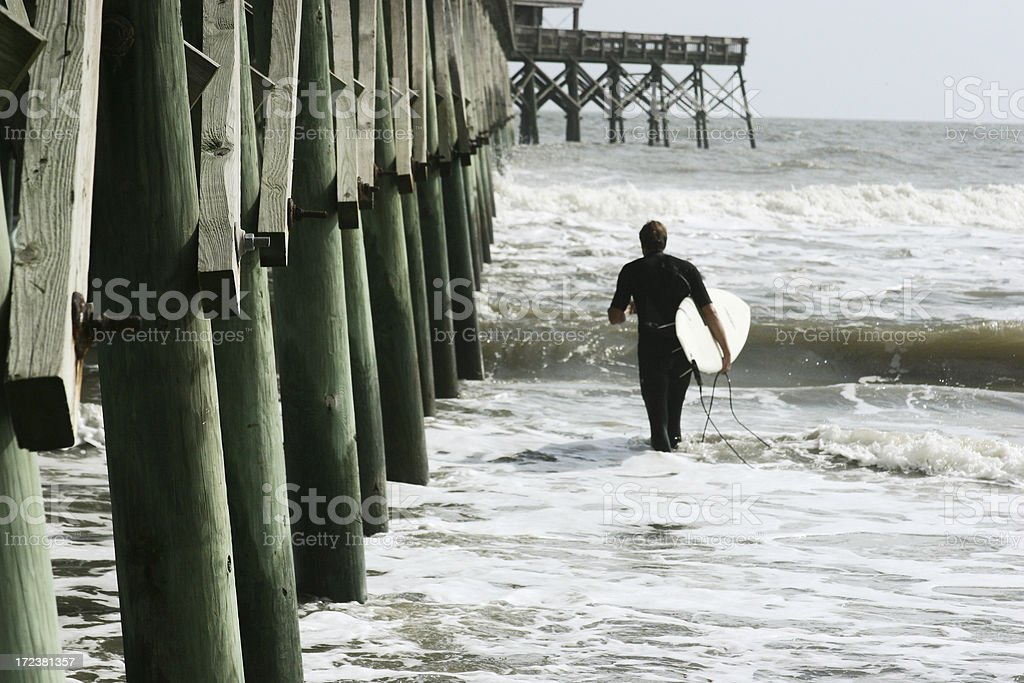 Surfer by pier stock photo