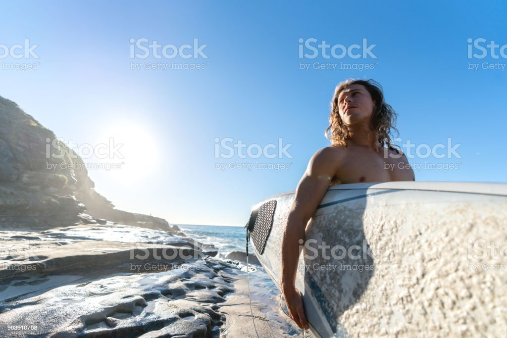 Surfer carrying his board at the beach - Royalty-free Adult Stock Photo