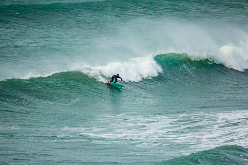 Surfer carving the waves, Fistral, Cornwall