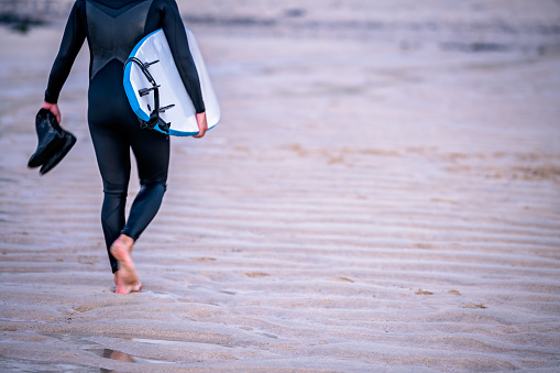 Surfer coming back from sea carrying board