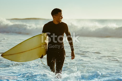Smiling young man with surfboard on the beach. African male coming out of the ocean after water surfing.