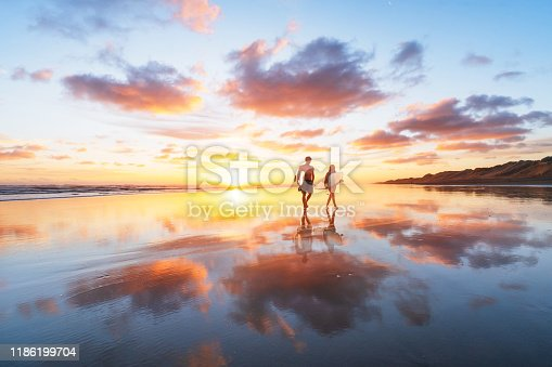 Surfer Couple heading back after a long day at Muriwai beach, Auckland, New Zealand.