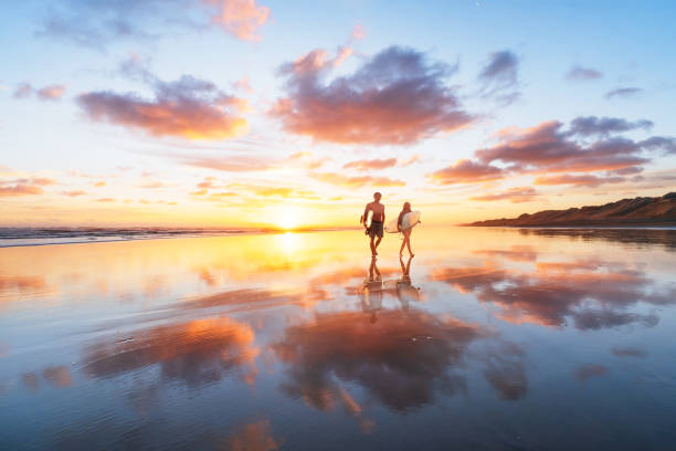 Surfer Couple heading back after a long day at beach. stock photo