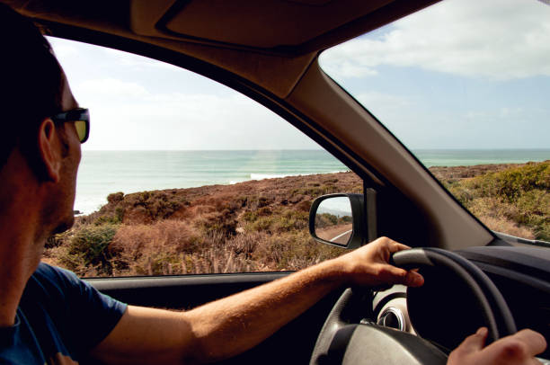 surfer driving car and looking at waves through car window - car view imagens e fotografias de stock