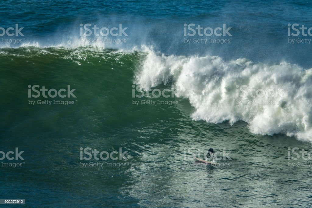 Surfer duck diving in a wave, stock photo