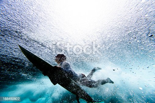 Surfer duck diving under reef break