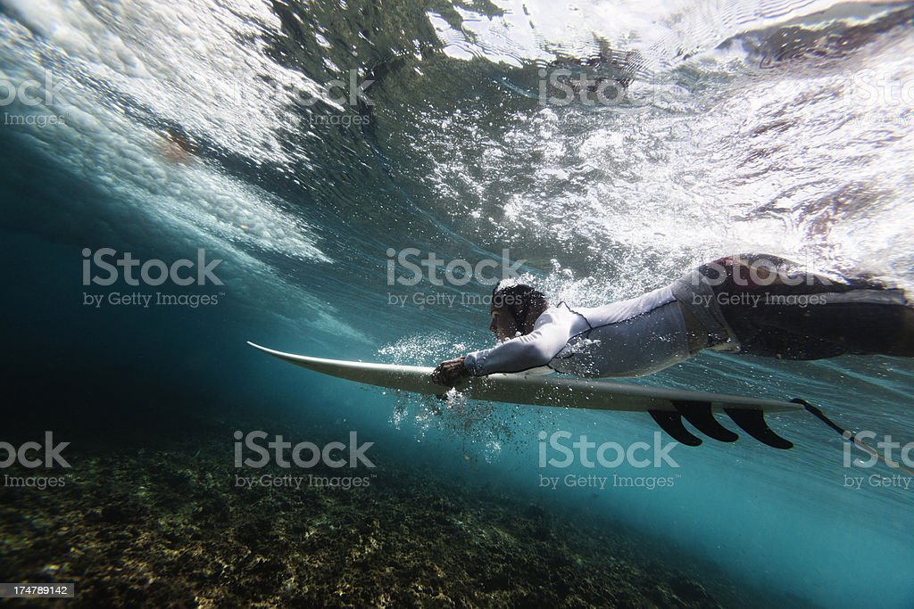 Surfer duck diving stock photo