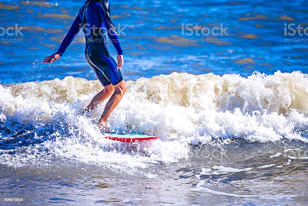surfer dude on a surfboard riding ocean wave stock photo