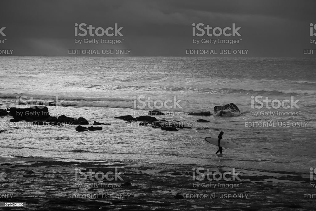 Surfer entering the water at Mollymook NSW stock photo