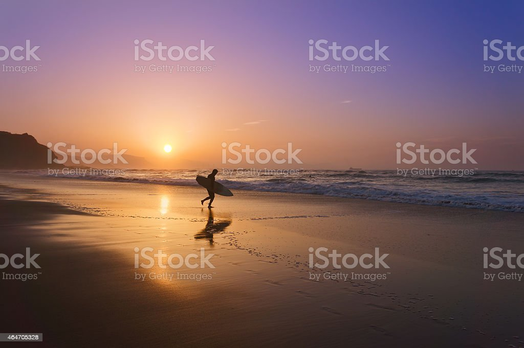 surfer entering water at sunset stock photo