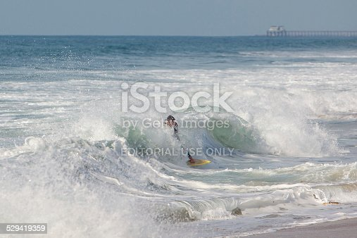 Carlsbad, California USA - December 11, 2014: A surfer in enveloped in a foamy wave as it breaks almost on shore. In the background the pier at Oceanside, CA is visible.