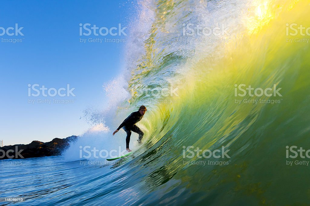 Surfer every riding a massive wave from side view stock photo