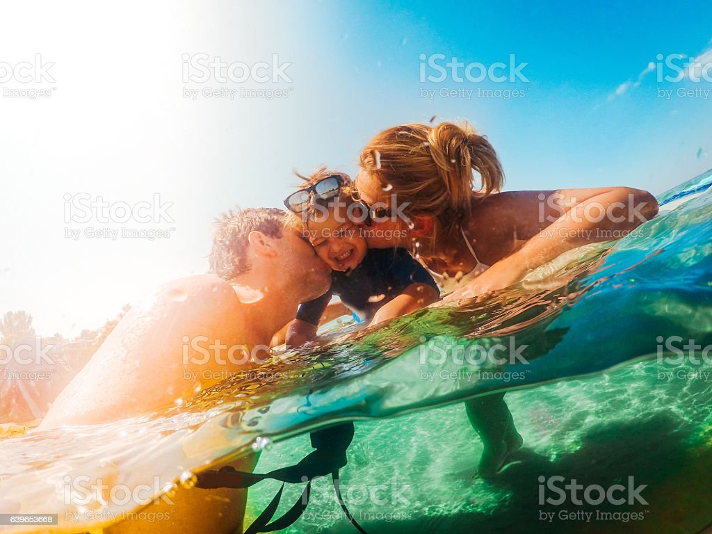 Surfer family in the sea stock photo
