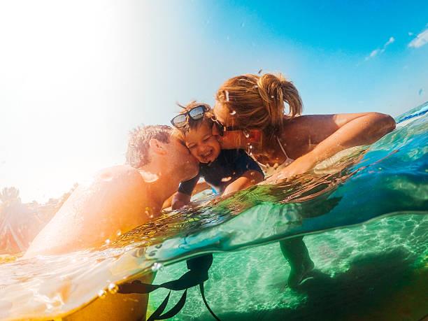 surfer family in the sea - urlaub in griechenland stock-fotos und bilder