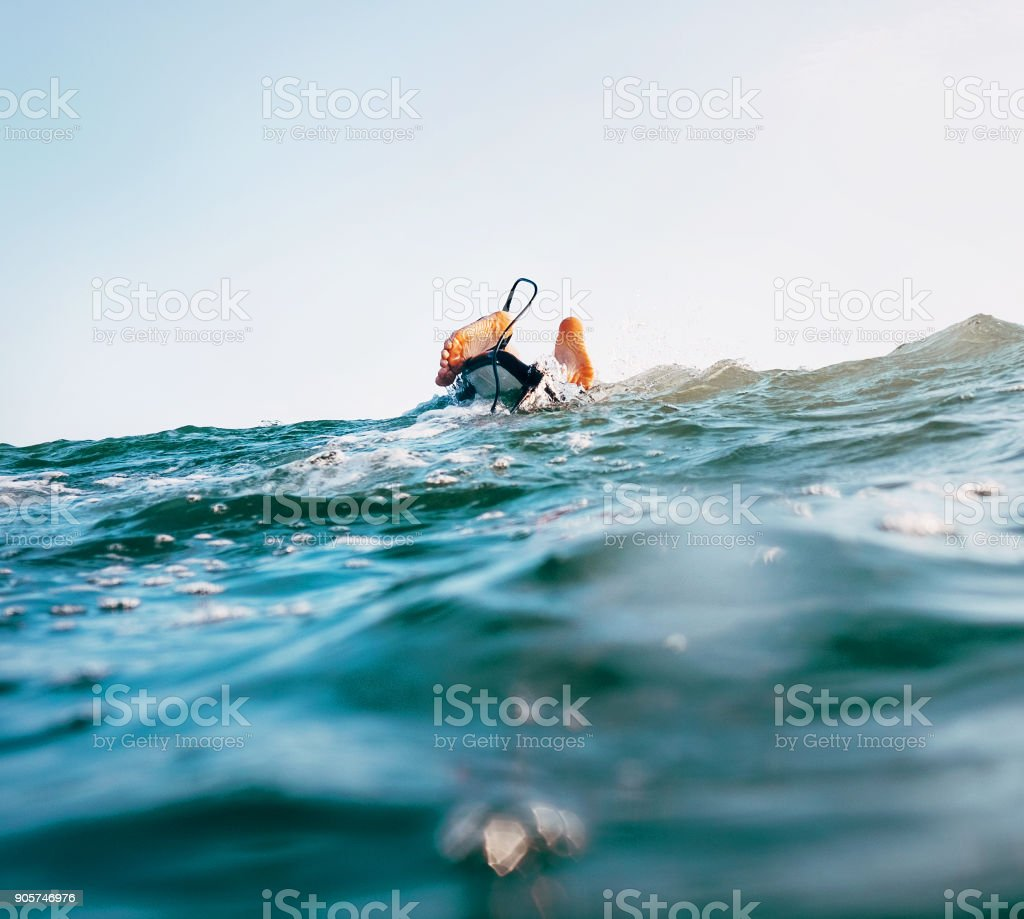Surfer feet with safety surfboard cord on the wave crest stock photo