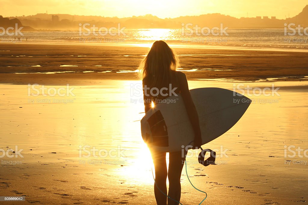 Surfer girl at sunset stock photo