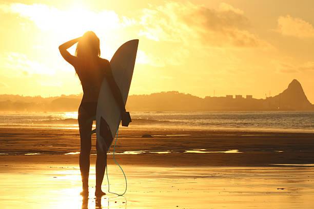 Chica surfista al atardecer - foto de stock