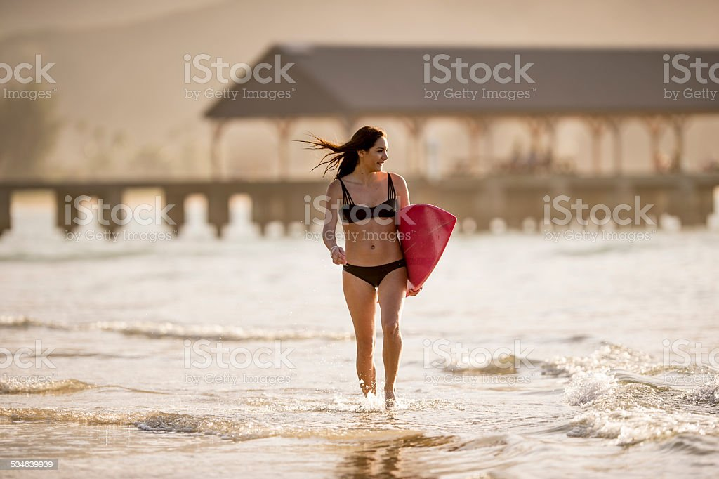 Surfer girl at the beach stock photo