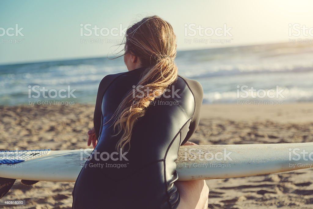 Surfer girl by the sea stock photo