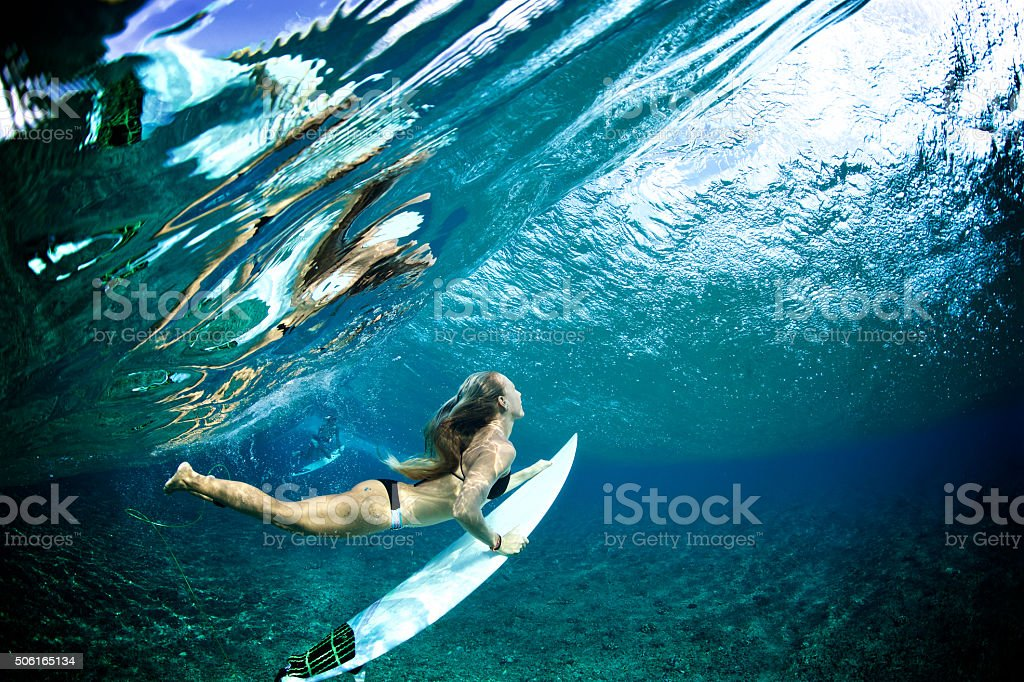 Surfer girl duckdives a wave with reflection stock photo