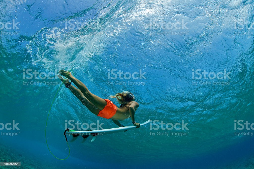 Surfer girl in orange shorts duck dives a wave stock photo