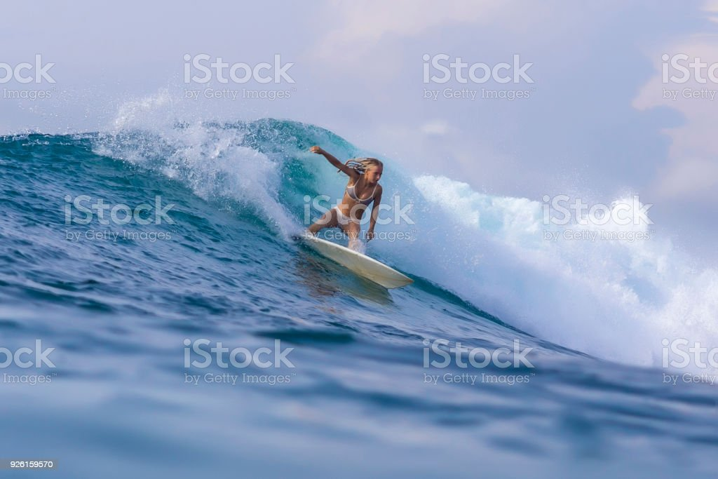 Surfer girl on a blue wave stock photo