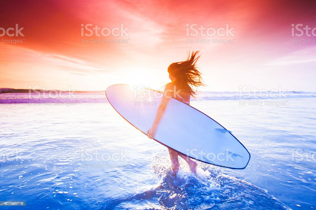 Surfer girl on beach at sunset stock photo