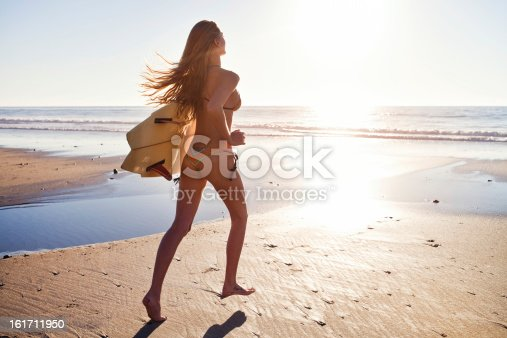 young woman running out to the ocean with surfboard