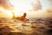 surfer girl paddling in ocean on white surfboard