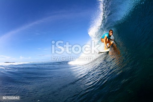 A surfer girl pulls into a smooth blue barrel