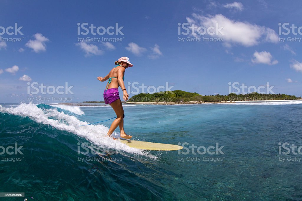 Surfer girl rides a longboard in the tropics stock photo
