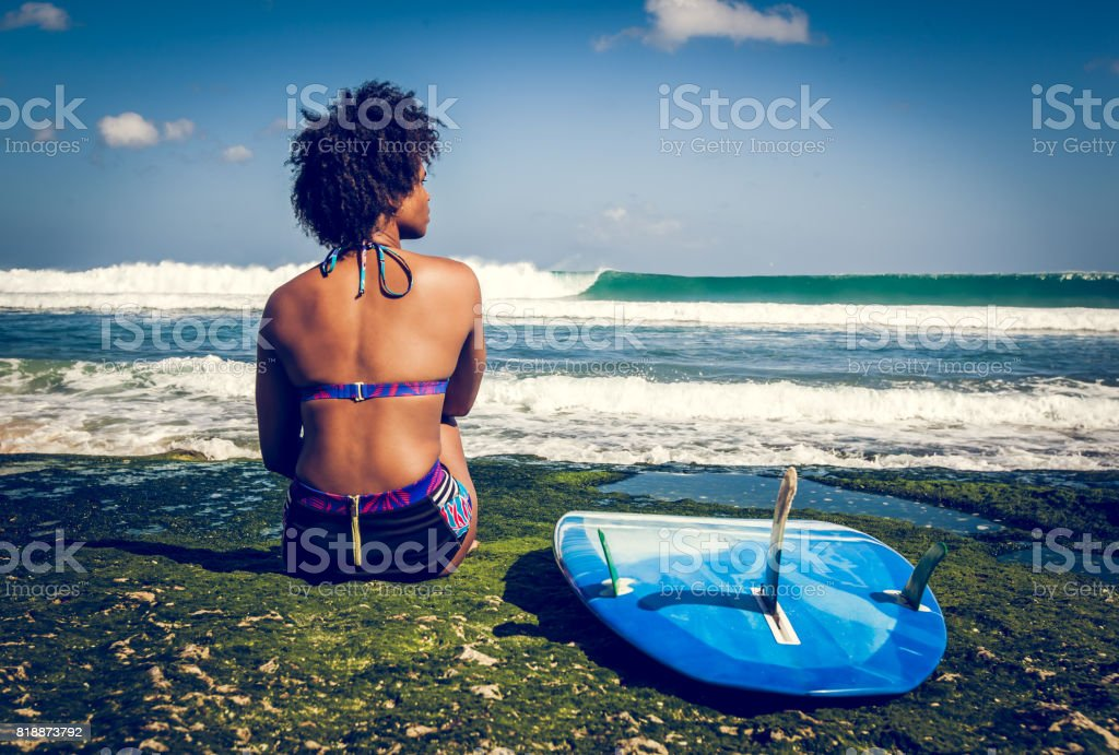 Surfer girl sitting next to blue longboard on the coral reef stock photo