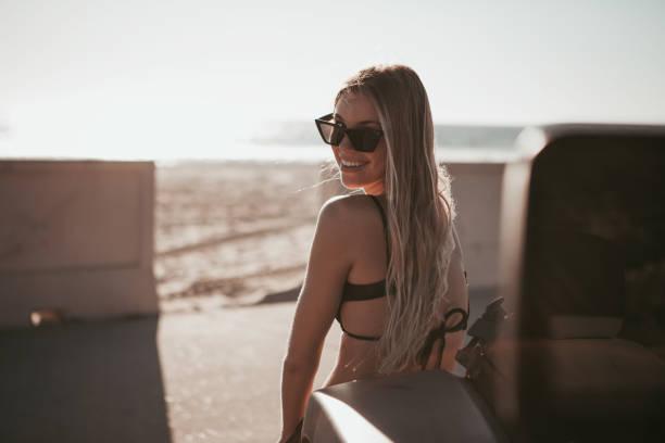 Surfer Mädchen steht an einem Auto am Strand. California Lebensstil – Foto