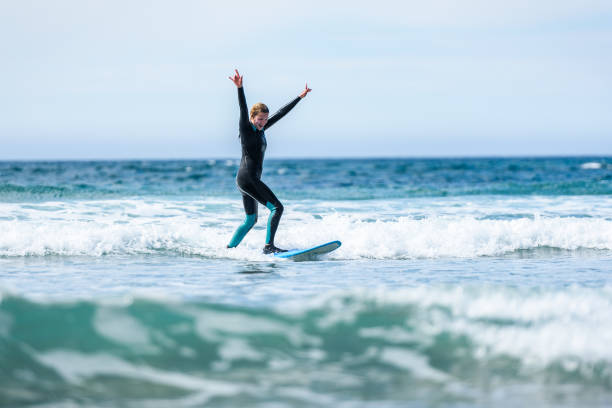 Surfer girl surfing with surfboard on waves in Atlantic ocean. Surfer girl surfing with surfboard on waves in Atlantic ocean. Woman in surfing wet suit is active surfing the waves of cold atlantic ocean in Galicia, Spain. wetsuit stock pictures, royalty-free photos & images