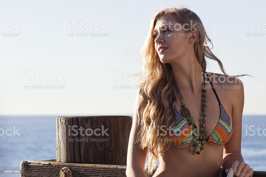 Surfer girl with long hair in bikini and beads by the ocean royalty-free stock photo