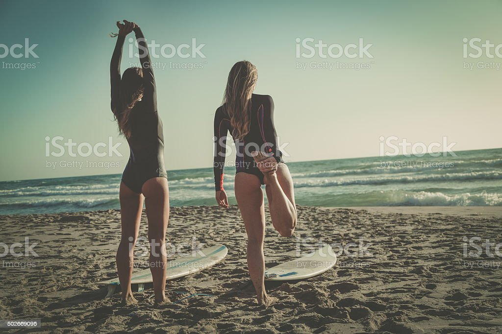 Surfer girls at sea before going surf stock photo