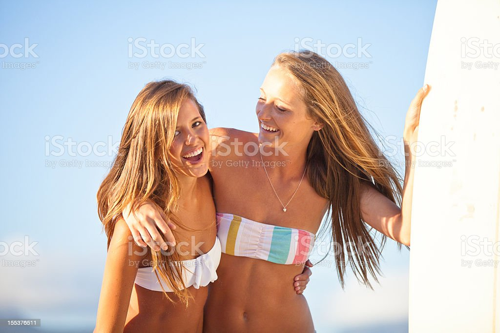 Surfer girls relaxing on the beach in summer royalty-free stock photo