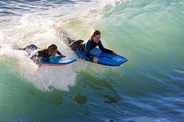 Surfer girls riding a wave at Seal Beach, CA stock photo