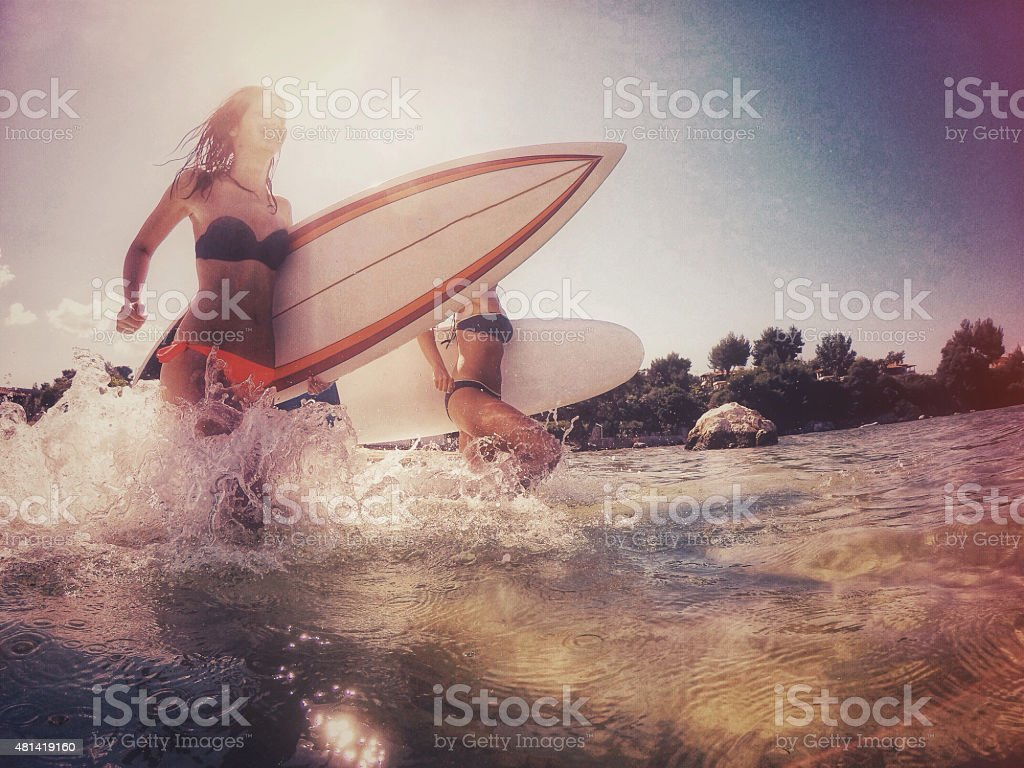 Surfer girls running through the water royalty-free stock photo