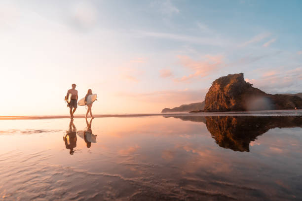 Surfer heading home at Piha Beach, Auckland, New Zealand. stock photo