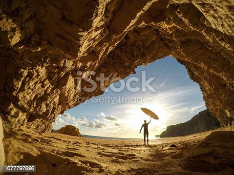 Surfer holding a surfboard up into the sun
