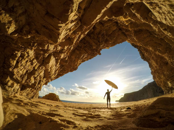Surfer holding a surfboard up into the sun stock photo