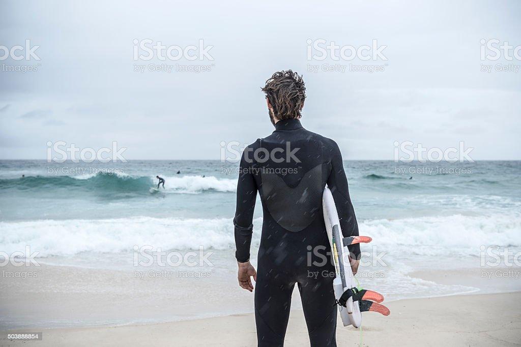 Surfer holding surfboard on Bondi Beach, rear view stock photo
