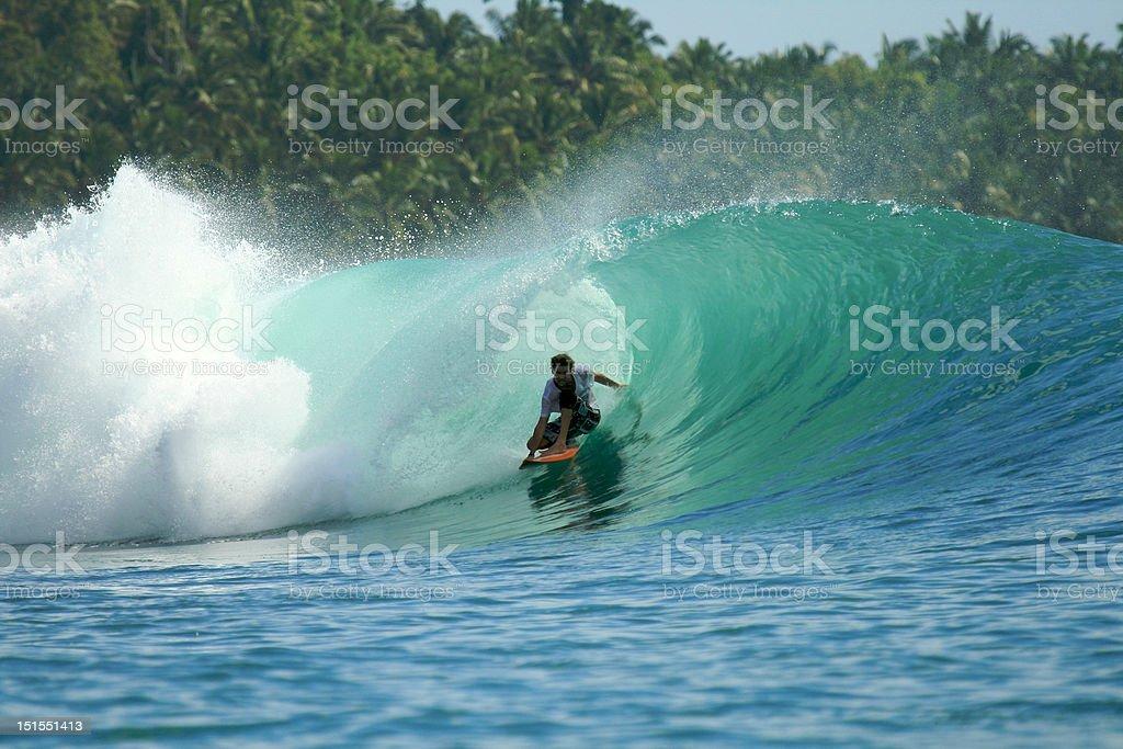 Surfer in barrel on green wave, Mentawai Islands, Indonesia stock photo