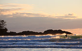 A male surfer in Tofino, British Columbia, Canada. Surfer is unrecognizable. Beautiful backlighting.