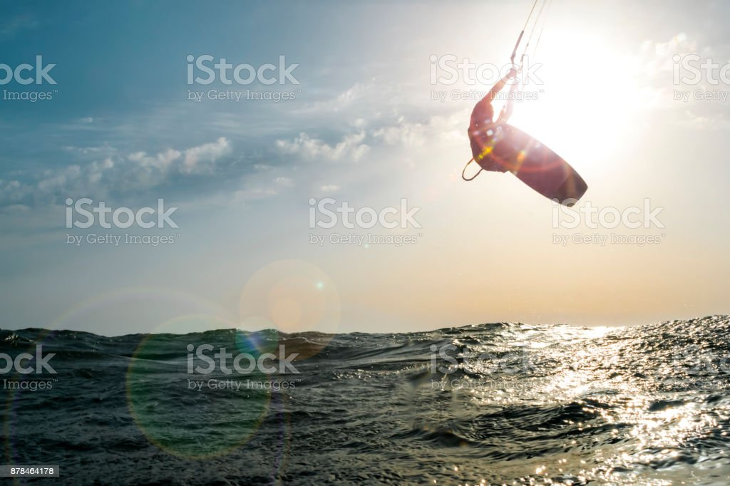 Surfer jumping at sunset over the golden sea stock photo