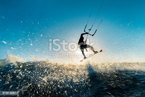 A surfer doing an amazing jump and splashing water in front of the sunset at the sea